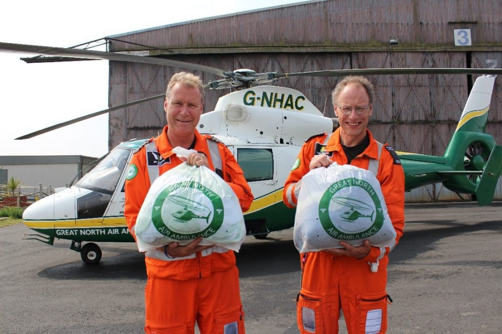 gnaas pilot jay steward and doctor theo weston with clothing collection bags