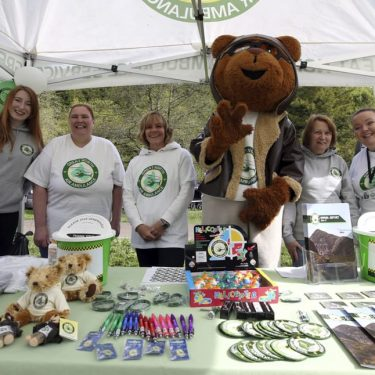 gnaas fundraisers and volunteers with merchandise at stall with miles the bear mascot