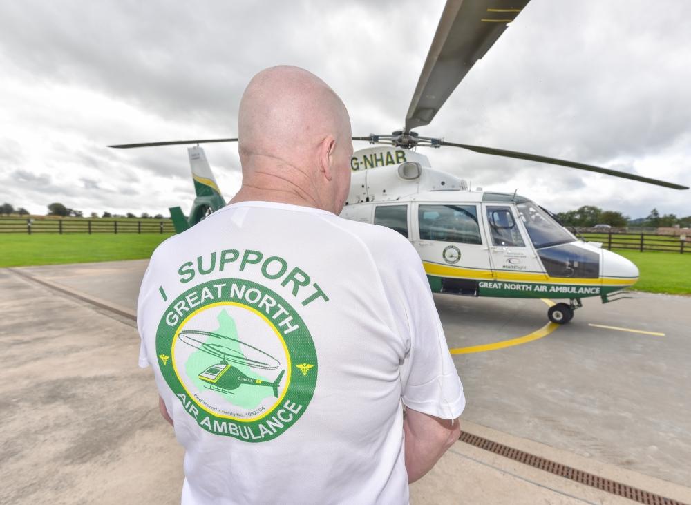 man wearing white gnaas logo shirt at langwathby base
